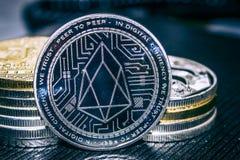 Muntstukcryptocurrency EOS op de achtergrond van een stapel muntstukken royalty-vrije stock afbeeldingen