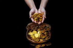 Muntstukgoud in damehand op partijen die gouden muntstukken op gebroken kruik witte achtergrond stapelen, Geldstapel voor bedrijf stock foto's