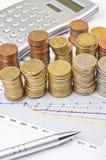 Muntstukken, calculator en pen over grafiek Royalty-vrije Stock Foto's