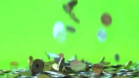Muntstukken die op een groene achtergrond, langzame motie vallen stock footage