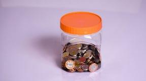 Muntstukken en Besparingen in een transparante fles stock foto
