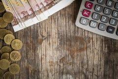Muntstukken en calculators op de oude houten lijst, financiënconcept Royalty-vrije Stock Afbeeldingen