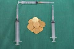 Muntstukken of geld met veelvoudige spuiten op chirurgie groene kleding cov stock fotografie