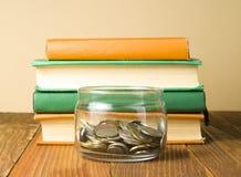 Muntstukken in glaskruik en stapel boeken op houten lijst Besparing, financiai en onderwijsconcept Stock Foto's