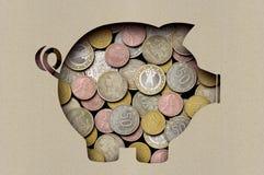 Muntstukken in het kader van een blad van document met een verwijderd beeld van een varken stock foto
