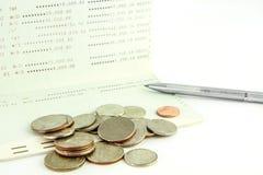 Muntstukken op rekeningsbankboekje met pen, Thais bad Stock Afbeeldingen