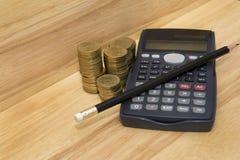 Muntstukken, potlood en calculator royalty-vrije stock fotografie