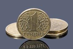 Muntstukken van één Oekraïense hryvnia op een grijze achtergrond Royalty-vrije Stock Foto's