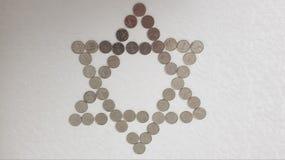 Muntstukken van één schikten de Israëlische sjekelmetaal op witte achtergrond in een vorm van Joodse zes puntenster royalty-vrije stock foto