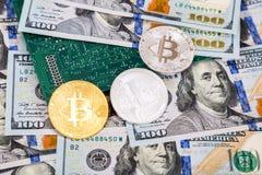 Muntstukken van cryptocurrency die over Amerikaans dollars en elektron liggen stock afbeeldingen