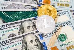 Muntstukken van cryptocurrency die over dollars en elektron liggen stock afbeelding