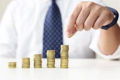Muntstukken van het bedrijfsmensen` s de hand gezette geld aan stapel muntstukken Stock Afbeelding
