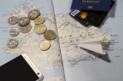 Muntstukken van IJsland, het vliegtuig, smartphone, het biometrische paspoort, de dollars, de muntstukken en de creditcards stock foto
