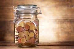 Muntstukken voor besparingen in de glaskruik stock foto's