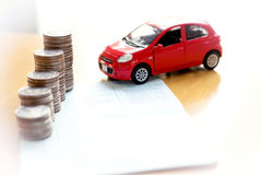 Muntstukkenstapel in kolommen op besparingsboek en auto op financiën Royalty-vrije Stock Foto