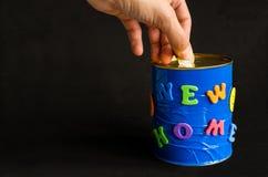 Muntstuktussenvoegsel in een met de hand gemaakte spaarpot met Nieuwe huisinschrijving op een zwarte achtergrond Stock Fotografie