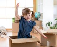 Muovendosi verso il nuovo appartamento bambino felice in scatola di cartone immagine stock libera da diritti