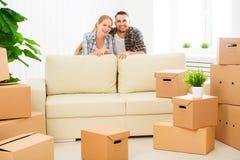 Muovendosi verso un nuovo appartamento Coppie e scatola di cartone felici della famiglia Immagini Stock