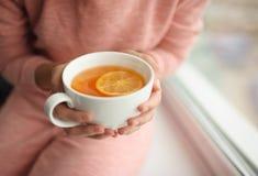Mup di tè caldo in mani ad una finestra Fine in su Fotografie Stock