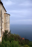 Mur antique avec peu de tour et mer disparaissant dans le ciel avec Photo libre de droits