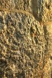 Mur antique de fort de bloc de pierre de Brown avec le fond de texture d'éclairage de coucher du soleil Images libres de droits