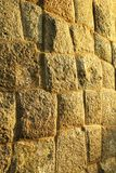 Mur antique de fort de bloc de pierre de Brown avec le fond de texture d'éclairage de coucher du soleil Photographie stock libre de droits