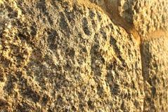Mur antique de fort de bloc de pierre de Brown avec le plan rapproché de texture d'éclairage de coucher du soleil Image libre de droits