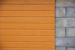 Mur avec des blocs de ciment de partie, panneautage en bois jaune de partie image libre de droits