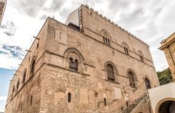 Mur avec les fenêtres à meneaux avec des marqueteries de pierre de lave du palais Steri Chiaramonte, Palerme, Sicile, Italie Photo libre de droits
