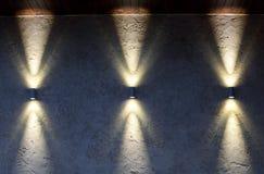 Mur avec trois lampes qui brillent en haut et en bas Image stock