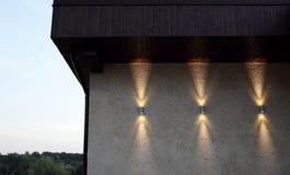 Mur avec trois lampes qui brillent en haut et en bas Images stock