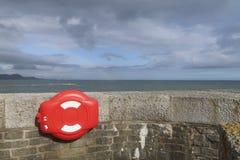 Mur avec un cas de bouée de sauvetage dans le coin avec la mer et le ciel opacifié Images libres de droits