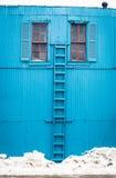 Mur bleu avec l'échelle en bois en hiver Photos libres de droits