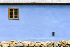 Mur bleu avec une base de fenêtre et de pierre Photo libre de droits