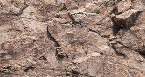Mur brun rugueux de roche, texture en pierre Photographie stock libre de droits
