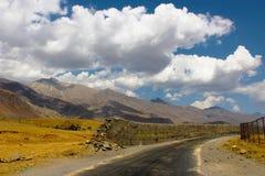 Mur cassé sur la route près de Kargil avec les nuages blancs image libre de droits