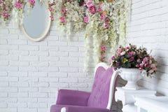 Mur décoré des fleurs et du miroir dans la pièce intérieure de grenier avec le sofa de style de vintage Photo libre de droits