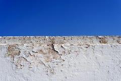 Mur de écaillement blanc et ciel bleu Photographie stock libre de droits