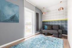 Mur de bâti et divan gris Image libre de droits