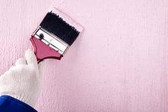 Mur de balai de peinture de peintre sur la couleur rose image stock
