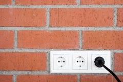 Mur de briques avec la prise de courant Photographie stock