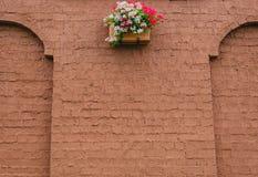 Mur de briques avec un lit des fleurs Photos stock