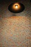 Mur de briques avec une lampe de plafond Image stock