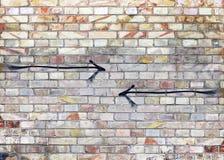 Mur de briques de couleur de vintage avec deux flèches noires opposées Photographie stock libre de droits