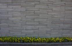 Mur de briques en pierre avec des fleurs de jardin. Photo stock