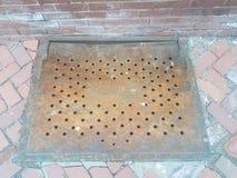 Mur de briques et trottoir rouges avec la porte de fer avec des trous photos libres de droits