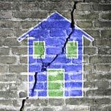 Mur de briques fendu avec une maison bleue dessinée là-dessus photo libre de droits