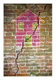 Mur de briques fendu avec une maison colorée dessinée là-dessus dans la forme de puzzle - image de concept photo stock