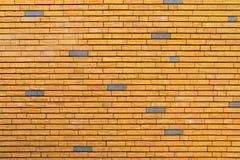 Mur de briques jaune entremêlé avec quelques briques grises Image stock