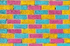 Mur de briques peint dans des couleurs jaunes, bleues et roses lumineuses Images libres de droits